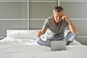 Senior man sitting up holding CD and staring at laptopの写真素材 [FYI03556295]