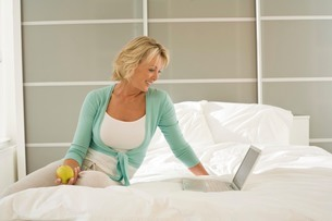 Mature woman sitting on bed browsing laptopの写真素材 [FYI03556298]