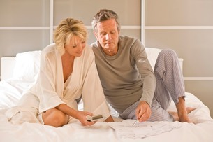Couple sitting up on bed using calculatorの写真素材 [FYI03556301]