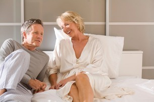 Couple reclining on bed chattingの写真素材 [FYI03556302]