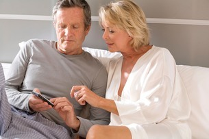 Couple sitting up in bed reading mobile phone textsの写真素材 [FYI03556303]