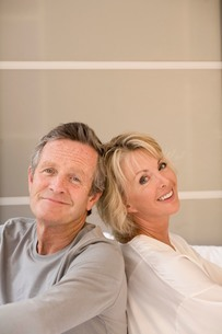 Portrait of happy couple back to back on bedの写真素材 [FYI03556304]