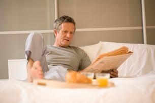 Senior man sitting up in bed reading newspaperの写真素材 [FYI03556305]