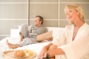 Couple relaxing on bed reading newspaper and listening to earphonesの写真素材 [FYI03556306]