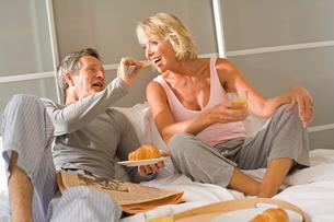 Romantic senior man feeding breakfast croissant to wife in bedの写真素材 [FYI03556307]