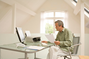 Senior man using computer and doing paperwork at home deskの写真素材 [FYI03556308]