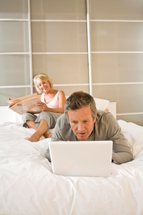 Couple on bed reading newspaper and using laptopの写真素材 [FYI03556309]