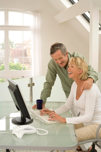 Couple using computer and laughing at home deskの写真素材 [FYI03556310]