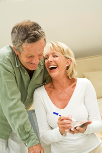 Couple making notes and laughing at homeの写真素材 [FYI03556312]