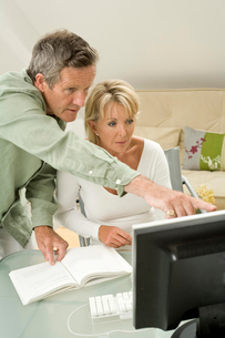 Couple using and pointing at computer on home deskの写真素材 [FYI03556313]