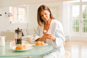 Mature woman at breakfast table reading mobile phone textsの写真素材 [FYI03556315]