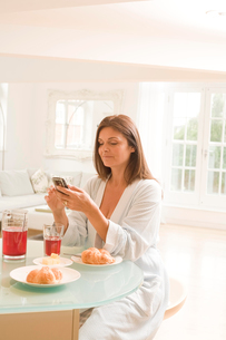 Mature woman at breakfast table reading mobile phone textsの写真素材 [FYI03556316]