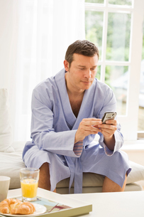 Mature man on sofa reading texts on mobile phone and having breakfastの写真素材 [FYI03556321]