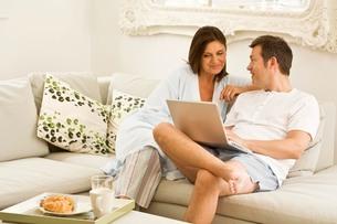Mature couple on sofa browsing laptop and having breakfastの写真素材 [FYI03556322]