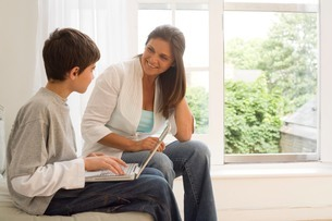 Boy and mother using laptop on sofaの写真素材 [FYI03556327]