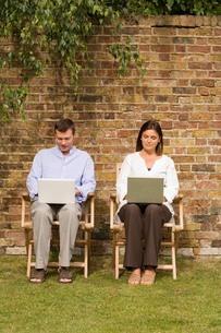 Mature couple sitting in garden using laptopsの写真素材 [FYI03556335]