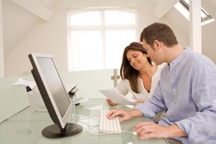Mature couple checking bills and paperwork on home desktop computerの写真素材 [FYI03556338]