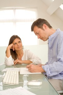 Mature couple checking bills and doing paperwork on home deskの写真素材 [FYI03556339]