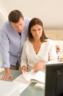 Mature couple checking bills on home desktop computerの写真素材 [FYI03556340]