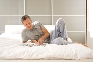 Senior man reclining on bed reading magazine and listening to earphonesの写真素材 [FYI03556341]