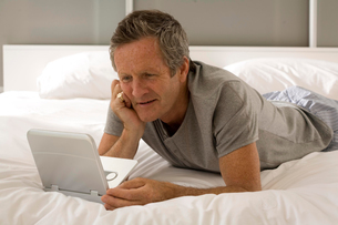 Puzzled senior man lying on bed staring at laptopの写真素材 [FYI03556342]