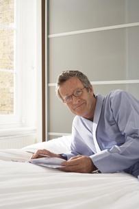 Portrait of senior man reclining on bed doing paperworkの写真素材 [FYI03556344]