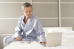 Senior man sitting on bed checking bills on laptopの写真素材 [FYI03556345]