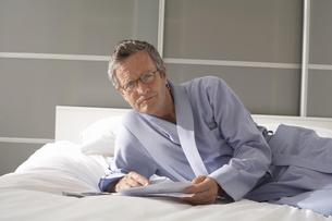Portrait of senior man reclining on bed checking billsの写真素材 [FYI03556346]