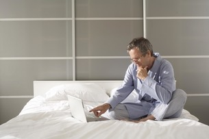 Puzzled senior man on bed pointing at laptopの写真素材 [FYI03556347]