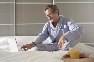 Puzzled senior man on bed typing on laptopの写真素材 [FYI03556348]