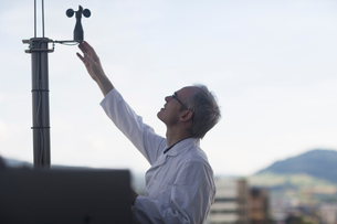 Male meteorologist measuring wind using anemometer at weather stationの写真素材 [FYI03556366]