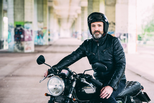 Mature male motorcyclist sitting on motorcycle wearing crash helmet under flyoverの写真素材 [FYI03556471]