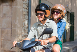 Young couple riding moped together through village, Majorca, Spainの写真素材 [FYI03556563]