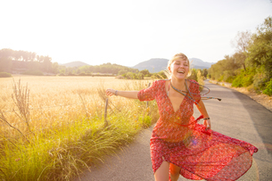 Young woman running and laughing on rural road, Majorca, Spainの写真素材 [FYI03556579]