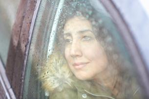 Mature woman gazing through car window in rainの写真素材 [FYI03556648]