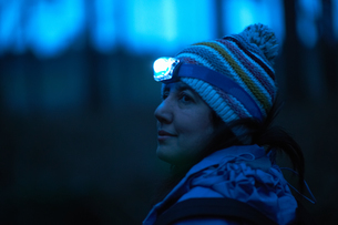 Female hiker wearing head torch looking over her shoulder from forest at nightの写真素材 [FYI03556651]