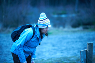 Female hiker wearing head torch reading in forest notice at duskの写真素材 [FYI03556657]