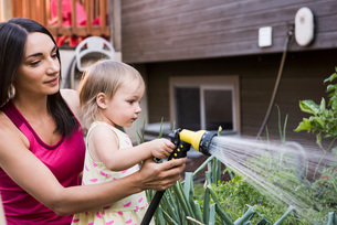 Mother and daughter in garden, watering plants together with hoseの写真素材 [FYI03556704]