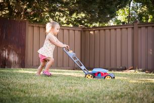 Young girl in garden, pushing toy lawn mowerの写真素材 [FYI03556720]