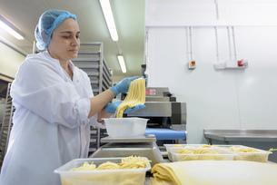 Female worker making tagliatelle in pasta factoryの写真素材 [FYI03556749]