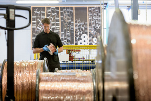 Worker inspecting copper cable in cable factoryの写真素材 [FYI03556822]