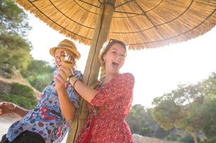 Couple under parasol holding ice cream cones, Majorca, Spainの写真素材 [FYI03556849]