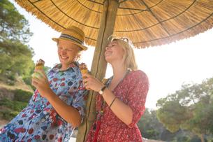 Couple under parasol holding ice cream cones smiling, Majorca, Spainの写真素材 [FYI03556850]