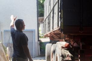 Male farmer guiding trailer into barnの写真素材 [FYI03556925]