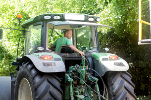Male farmer looking back to reverse tractorの写真素材 [FYI03556928]