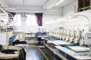 Rows of programmed embroidery machines speed stitching  cloth in clothing factoryの写真素材 [FYI03556957]