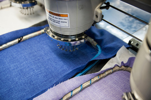 Programmed embroidery machines speed stitching blue and purple cloth in clothing factoryの写真素材 [FYI03556958]
