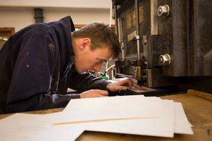 Young male printer preparing printing machinery in printing press workshopの写真素材 [FYI03556966]