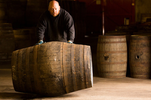 Portrait of worker rolling whisky cask in whisky distilleryの写真素材 [FYI03556976]
