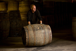 Worker rolling whisky cask in whisky distilleryの写真素材 [FYI03556981]